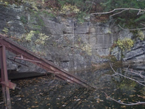 The conveyor ended somewhere in the bottomless quarry, now filled with dark water